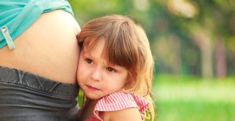 Bilder eines Kindes, dass bei seiner schwangeren Mutter an Ihrem Bauch lauscht.